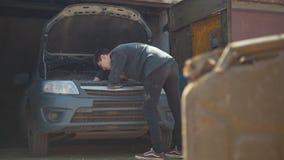 Kanister steht vor Reparaturauto des jungen Mannes in der Garage stock footage