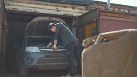 Kanister steht vor Reparaturauto des jungen Mannes in der Garage stock video footage