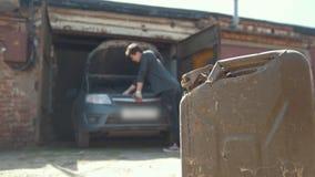 Kanister steht vor Reparaturautomotor des jungen Mannes in der Garage stock video footage