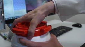 Kanister utan etikett för behållare för kemisk forskareöppning vit plast- med kemikalieer på laboratoriumtabellen royaltyfri bild