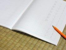 Kanji practice. Practicing kanji on a tatami Stock Image