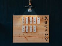 Kanji Printed Tags Hanged on Brown Wooden Board Lighted by Pendant Lamp Royalty Free Stock Image