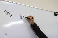 Kanji on Whiteboard. A teacher is writing Kanji (Japanese Chinese Characters) on the whiteboard Stock Photos