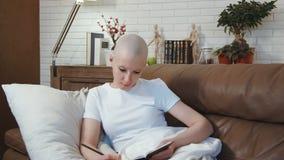 Kanker geduldige vrouw die op de bank liggen en een boek lezen stock video