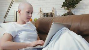 Kanker geduldige vrouw die op de bank liggen en haar laptop met behulp van stock footage