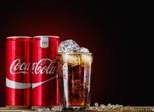 Kann und Glas von Coca-Cola mit Eis auf hölzernem Hintergrund Stockfotografie