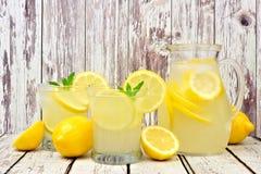 Kanna av lemonad med exponeringsglas på lantligt vitt trä Arkivfoto