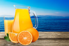 Kanna med highball av orange fruktsaft med apelsiner Royaltyfri Foto