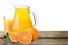 Kanna med highball av orange fruktsaft med apelsiner Royaltyfri Bild