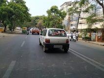 Kannada Film Actor Rebel Star Ambarish Sticker and Quotes back of the White Maruti Zen Car. Bangalore Asphalt Road with Big Trees