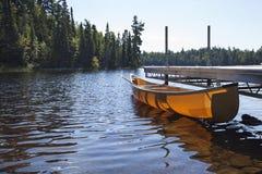 Kano aan een dok op een noordelijk meer dat van Minnesota wordt gebonden royalty-vrije stock foto