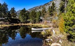Kano onbeweeglijk langs de kust van stil meer tijdens de herfst stock foto's