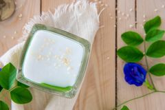 `Kanom Peak Poon Bai Tuey Kati Sod` Thai Sweet. Sweet Pudding, Natural Green Color From Pandan Leaf And Topping With Coconut Milk Cream And Saseme royalty free stock photo