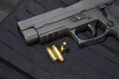 kanon en 9mm kogels op een kogelvrij vest royalty-vrije stock afbeelding
