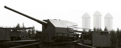 Kanon met drie moderne gebouwen in mist op backg Stock Foto
