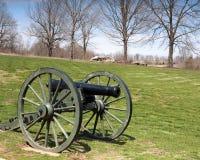 Kanone, die auf Gras mit Bäumen und Felsen im Hintergrund sitzt Lizenzfreies Stockbild