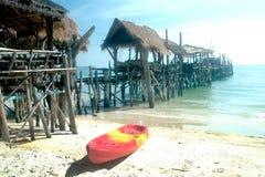 Kanota på stranden och den traditionella träbron Royaltyfri Bild