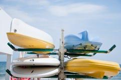 Kanoter av olika färger lägger i sanden royaltyfri foto