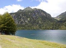 Kanoter i en sjö mellan berg arkivbild