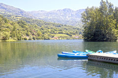 Kanoter i en sjö nära en omgiven by arkivfoto