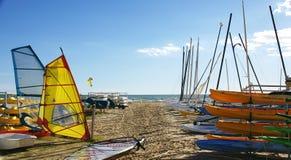 Kanoter, master och bräden av Kitesurf i stranden av Castelldefels arkivfoto