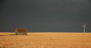 Kansas. A small old shack is seen across from a modern wind farm turbine on a stormy day in central Kansas Royalty Free Stock Photo