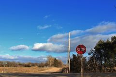 Kansas Country Road with blue sky,clouds, and a stop sign. stock images