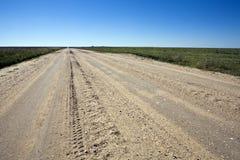 Kansas Farm Road. Graded dirt and gravel road runs straight across Kansas farmlands stock photo