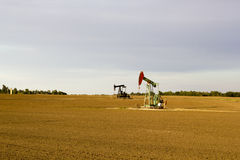 Kansas oil field. Kansas oil & gas pumping units in open field with blue skies Stock Image