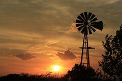 Kansas-Sonnenuntergang-Windmühle mit grauem Himmel und weißen Wolken lizenzfreie stockbilder