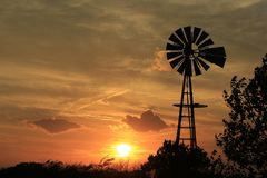 Kansas Sunset Windmill with gray sky and white clouds royalty free stock images