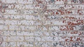 Kanstödda röda vita grå färgblått målar tegelstenväggen Arkivbild