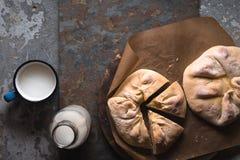 Kant-en-klare khachapuri met kaas en stukken op perkament en melk in een flessendiagonaal Royalty-vrije Stock Fotografie