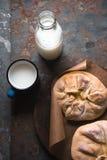 Kant-en-klare khachapuri met kaas op perkament en melk in een fles Stock Afbeelding