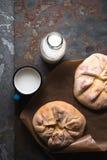 Kant-en-klare khachapuri met kaas op perkament en melk in een flessendiagonaal Stock Foto's