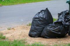 Kant van de weg van de stapel de zwarte vuilniszak in de stad Stock Foto's