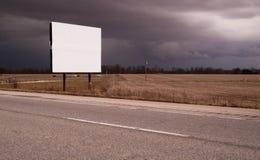 Kant van de wegaanplakbord die Middelgrote Donkere Stormachtige Hemel adverteren Stock Afbeeldingen