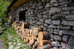 Kant van oud plattelandshuisje met houten stapel Stock Afbeelding