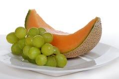 Kantaloep en groene druiven op witte plaat Stock Foto's