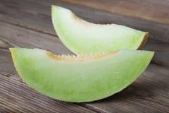 Kantaloep gele verse die meloen met gesneden meloen, houten lijst, grijze achtergrond wordt geïsoleerd De zomervruchten stock foto's