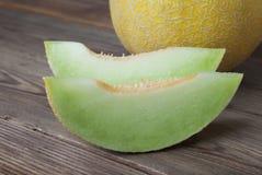 Kantaloep gele verse die meloen met gesneden meloen, houten lijst, grijze achtergrond wordt geïsoleerd De zomervruchten royalty-vrije stock fotografie