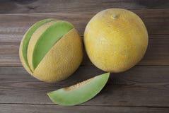 Kantaloep gele verse die meloen met gesneden meloen, houten lijst, grijze achtergrond wordt geïsoleerd De zomervruchten stock afbeeldingen