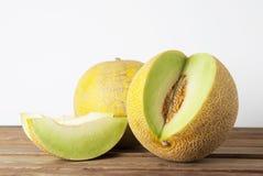 Kantaloep gele verse die meloen met gesneden meloen, houten lijst, grijze achtergrond wordt geïsoleerd De zomervruchten stock foto