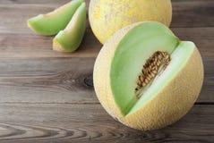 Kantaloep gele verse die meloen met gesneden meloen, houten lijst, grijze achtergrond wordt geïsoleerd De zomervruchten stock afbeelding