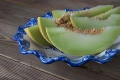 Kantaloep gele verse die meloen met gesneden meloen wordt geïsoleerd, in mooie uitstekende blauwe plaat, houten lijstachtergrond  royalty-vrije stock afbeelding