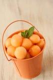 Kantalup piłki W Pomarańczowym wiadrze obrazy royalty free