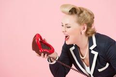 Kanter och rop Blont utformat kvinnarop för stift upp som ska ringas Damuttryck över telefonen Flicka på Rose bakgrund Fotografering för Bildbyråer