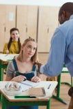 Kantjusterad bild av afrikansk amerikanläraren som talar till kvinnliga tonårs- studenter för högstadium arkivbilder