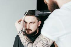 kantjusterad bild av barberaren som torkar kundhår royaltyfria bilder