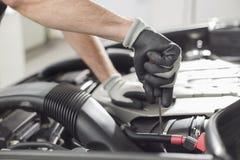 Kantjusterad bild av bilmekanikern som reparerar bilen i billager Arkivfoton